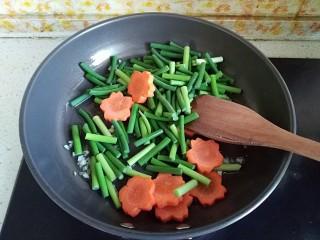 糖醋虎皮鹌鹑蛋,倒入蒜薹段和胡萝卜花片煸炒