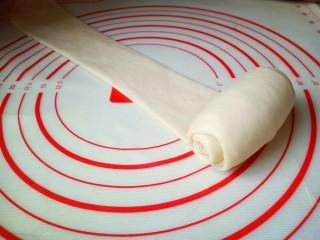 原味吐司,取一块面团用擀面杖擀长舌状,再卷起来,从上往下卷,依次做完。