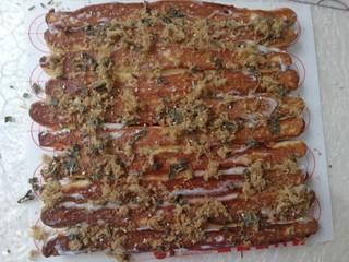 海苔肉松面包卷,烤好的面包倒过来,抹上一层沙拉酱,撒上肉松和海苔碎,然后将面包卷起来,切成大小合适的块。
