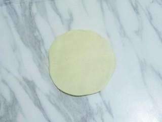 蛋黄酥,按扁,用擀面杖擀成中间稍厚,四周稍薄的面皮