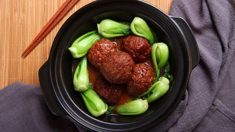 红烧狮子头,青菜铺在碗底四周,将狮子头摆于盘中,倒入汁水,这道淮扬名菜就做好啦