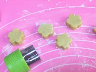 烧仙草,另一半红薯面团压成饼状,用模具压出花朵形状。同样的,紫薯面团也同样做好。