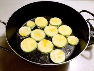 香煎西葫芦鸡蛋饼,锅内加入少许大豆色拉油烧热,加入裹好淀粉和鸡蛋液的西葫芦片,小火煎制