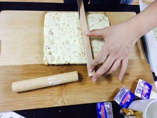 适合新手的原味花生牛轧糖,稍微冷却之后用辅助工具先在牛轧糖上面划出痕迹,之后会比较好切