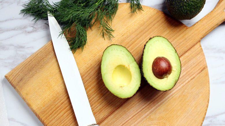 绿色美食+烟熏三文鱼牛油果沙拉,牛油果纵向对半切至果核处,双手拧开。