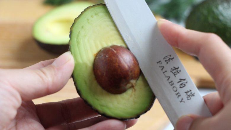 绿色美食+烟熏三文鱼牛油果沙拉,刀卡住果核,一手拿住牛油果,一手握住刀柄左右转动,取出果核,操作如图。