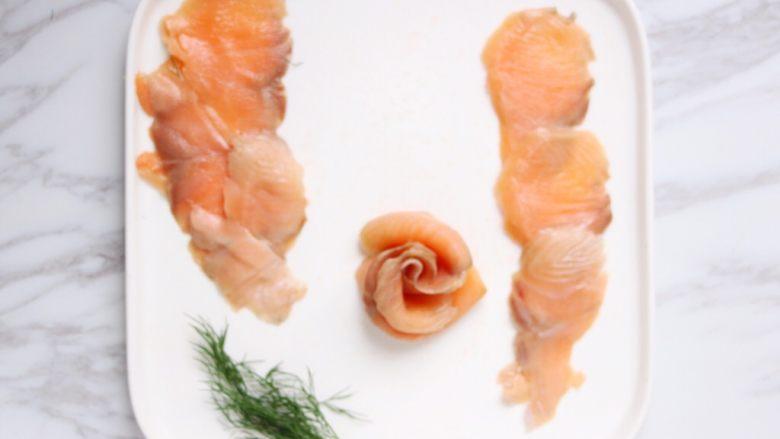 绿色美食+烟熏三文鱼牛油果沙拉,如图三片依次叠好,卷起来就成花的形状了(五片鱼卷起来更好看),花边向外翻翻,放到沙拉盘中。
