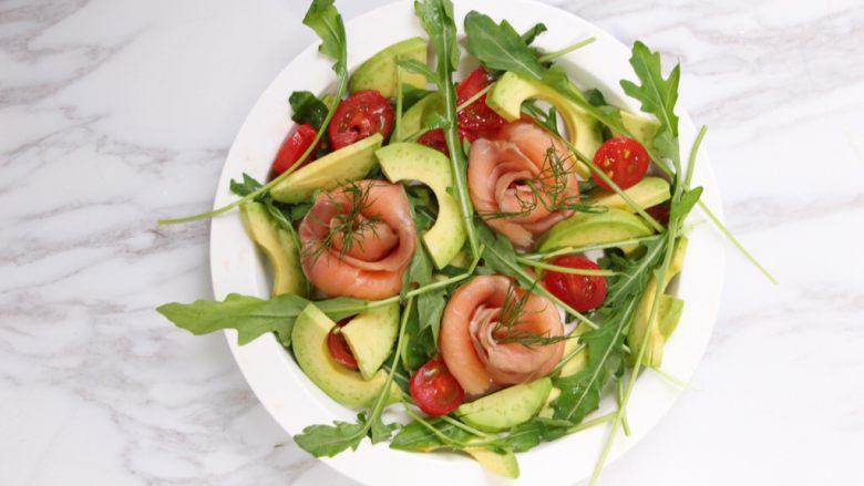 绿色美食+烟熏三文鱼牛油果沙拉,将小番茄切成对半,和芝麻菜、牛油果肉一起混合放入沙拉盘。三文鱼玫瑰花上缀上莳萝。