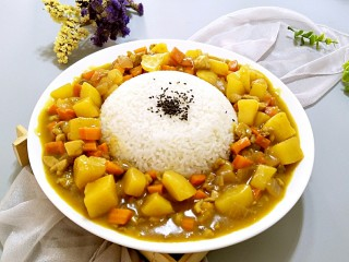 鸡肉咖喱饭,把做好的咖喱用勺子整齐的盛入到米饭周围,米饭上撒点黑芝麻就显得更好看了,这样就可以开动啦!
