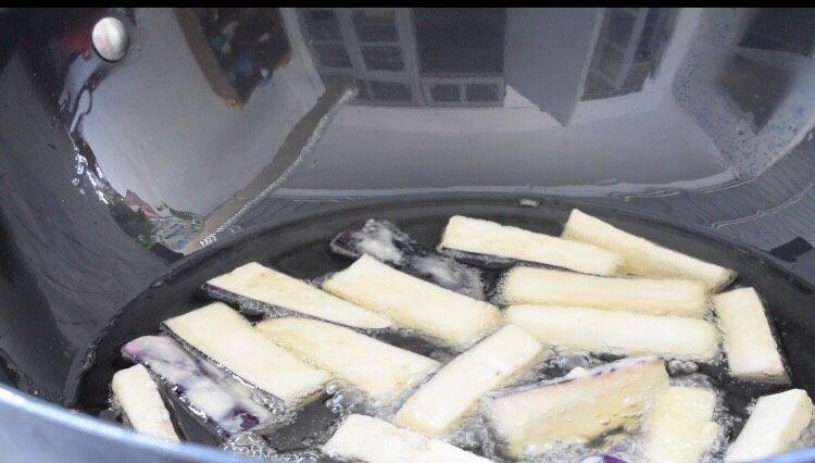 避风塘茄子,锅中的油烧至六成热时放入茄子