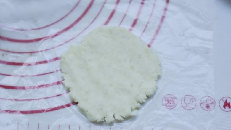 白薯豆沙茶巾绞,取一个白薯泥球,放在保鲜膜上,隔着袋子压成片状。
