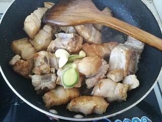 #那一抹家乡味#妈妈菜干豆角烧肉,继续加入一些蒜瓣和和生姜,中火翻炒。