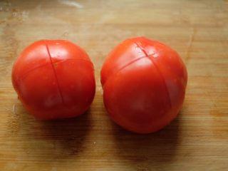 【再添一碗饭】の番茄牛腩锅,番茄洗净,顶部划十字,放入沸水中焯烫