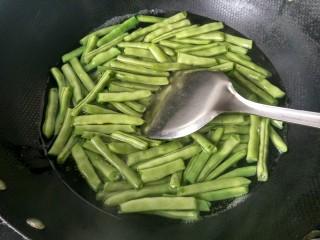 绿色美食+干锅四季豆(微辣),水开后倒入洗干净的四季豆。