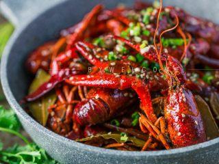 麻辣小龙虾,出锅后倒入盘中,撒上少许白芝麻和葱花装饰即可。