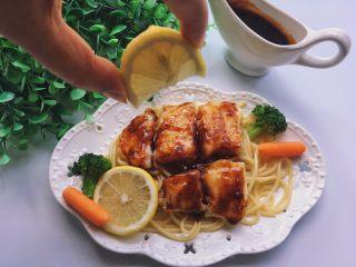 黑椒巴沙鱼意面,盘底铺意面,摆上鱼柳,倒上酱汁,吃前挤上柠檬汁~
