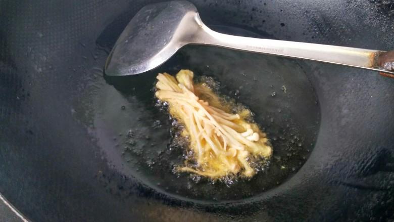 油炸金针菇,将金针菇放入锅中油炸。