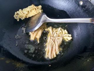 油炸金针菇,将炸好的金针菇放旁边沥一下油再夹出,然后依次放入剩下的金针菇。