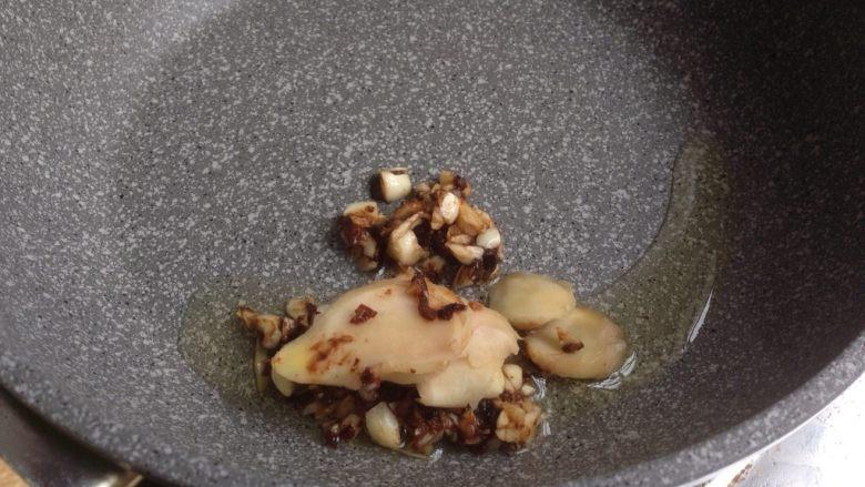 苦瓜焖鸭,不沾锅加10克油烧热后,加入姜片和豆豉蒜蓉