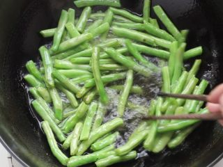 干煸豆角,锅中稍多些的油,七成热放入豆角剪炸,炸至豆角表面起泡,捞出沥油。