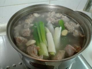 羊油香飘羊排汤,羊排锅烧开了,撇去浮沫,放进大葱,姜片,蒜头,八角和花椒纱布包烧开,调小火慢炖两个小时
