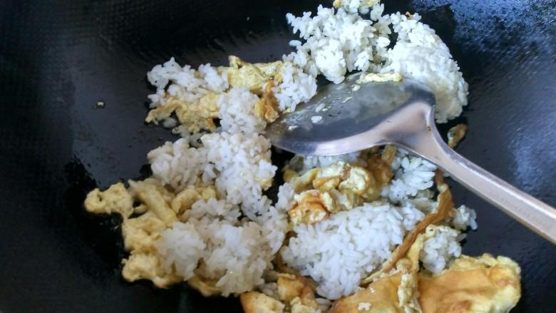 五彩炒饭,把剩米饭倒入锅中,将米饭炒散。