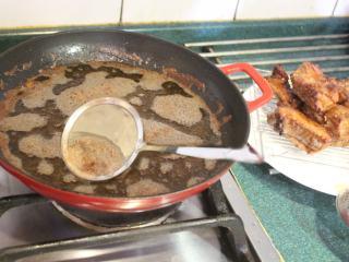 香酥排骨,将排骨捞起滤油,并捞掉油面浮沫。