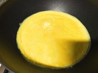 零失败的蛋包饭,隔夜饭的春天,鸡蛋打散,倒入锅中,旋转锅柄,使蛋液成均匀圆形。