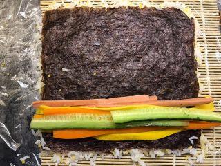 肉松寿司,依次把黄瓜、胡萝卜、香肠、鸡蛋条铺上去