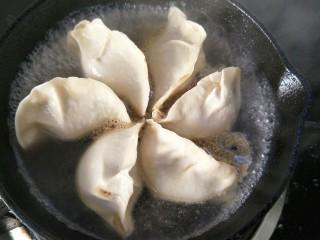 抱蛋煎饺,小火煎一会后倒入抹过饺子一半的水,中火煎煮。