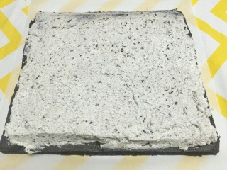 奥利奥竹炭卷,将淡奶油涂抹在蛋糕上,靠自己的这一边涂抹厚一些,越往前端沫的越薄,这样卷出来的蛋糕卷奶油才不会挤压出来。