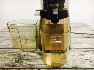 #冬喝热饮夏吃冰# 自制鲜橙汁,把两个容器分别放在榨汁机的出汁口和出渣口处。