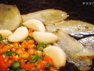麻辣香锅   🌶辣,是饭桌上不可或缺的一味,锅中倒入之前做好的葱油和香料油。加入姜片、蒜、小米椒后爆炒。