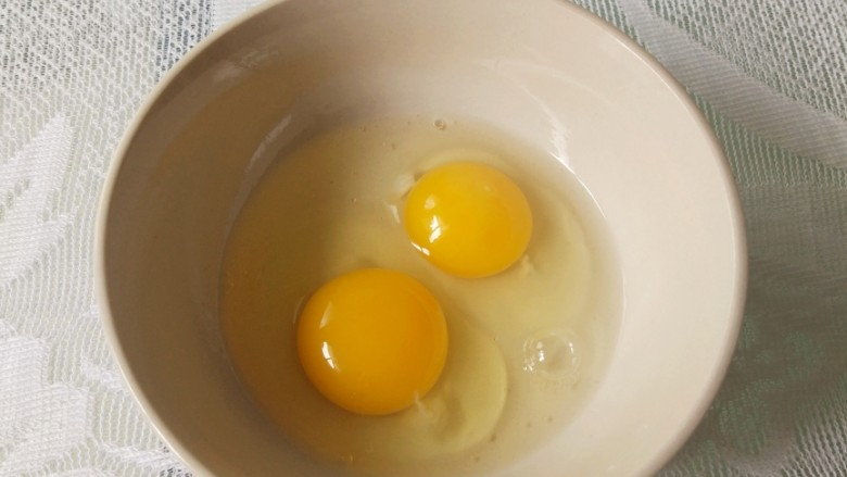 番茄炒蛋,鸡蛋敲入碗中