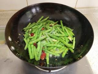 干煸四季豆,全程中小火,无需加水,慢慢把四季豆煸至干香,加味精,翻炒均匀,起锅装盘。