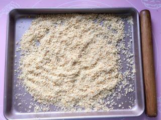 花生酥~#家有烤箱#,将熟花生米放在烤盘中,用擀面杖压碎,不要压成泥,稍微带点颗粒,吃起来口感更好。