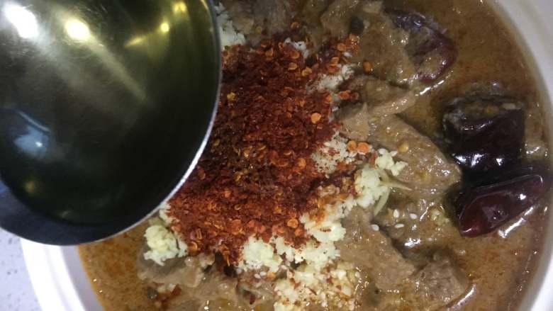 水煮牛肉,锅中烧热 色拉油后,用勺子将油淋在碗中的辣椒粉上。