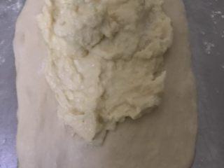 天然酵母榴莲奶酪软欧,取一个白色面团擀开,抹上榴莲奶酪馅,四周不要抹,底部留多点不要抹。