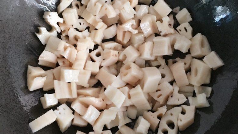 糖醋藕丁,炒锅放入适量油烧至七成热时,倒入藕丁翻炒。