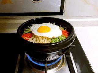 石锅拌饭,把做好的石锅饭放到燃气灶上加热,听到里面的米饭有滋滋的响声就是烧好了