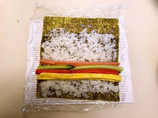 寿司,在米饭上加入蛋皮,胡萝卜条,瓜条,火腿条