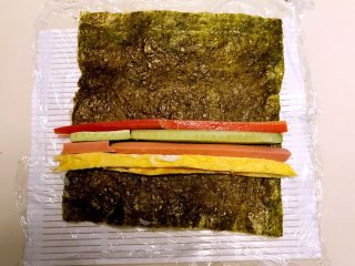 寿司,把紫菜翻身,有米饭的一面向下,在紫菜上加入蛋皮,火腿条,瓜条和胡箩卜条