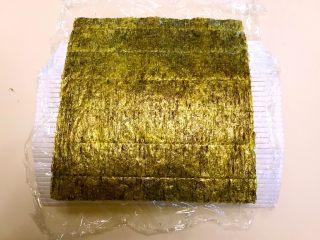 寿司,再取一片海苔,粗面向上放在保鲜膜上