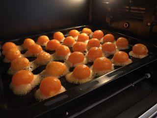 中式点心—酥掉渣的蛋黄酥,预热烤箱,上下管180度。同时将咸蛋黄取出摆放在烤盘上(最好垫一层锡纸或吸油纸),送入烤箱,烤7min左右,烤到蛋黄冒油就可以了。  烤好的咸蛋黄连盘取出,放置一旁降温。  我们可以把500g红豆沙(我买的低糖红豆沙,没有自己炒)平均分成20份,分豆沙的过程中,蛋黄就差不多降温完毕啦。  接着把咸蛋黄包入红豆沙里面,虎口收口(方法同下面的油皮包油酥)。把包好的馅料摆放烤盘中,并覆盖保鲜膜,送入冰箱冷藏。冷藏后的馅料会变得更结实,方便包制。