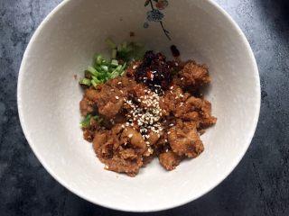 四川乐山名小吃—粉蒸肉卡饼,取适量粉蒸肉放入香菜小葱碗中,加入适量油辣椒,芝麻拌匀。