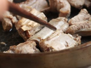 川香土豆炖排骨,另起锅,加油烧热,放入排骨略煎。