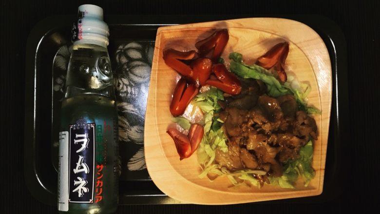 姜汁豚肉定食,在盘里铺上菜丝,放上猪肉片,淋上平锅里剩下的酱汁。煎好小热狗(可以加一个煎蛋)后盛盘。