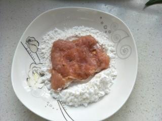 炸猪排,把腌制好的肉放淀粉中反正面沾匀。