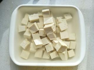 麻婆豆腐,盆里倒入热水,加适量的盐,把豆腐切块浸泡。