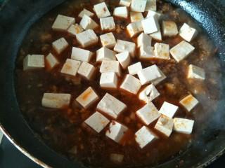 麻婆豆腐,下入浸泡好的豆腐块继续煮。